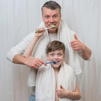 Father's day brushing teeth alongside son concept