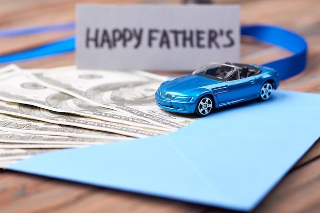 父の日カードと車。封筒とリボンで現金。お父さんの夢をかなえましょう。