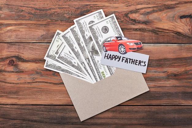父の日カードとドル。封筒に紙の車。スーパーパパへの素晴らしいプレゼント。