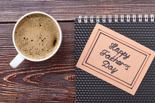 Father's day card and coffee. cup of coffee and notebook. tasty drink that refreshes.