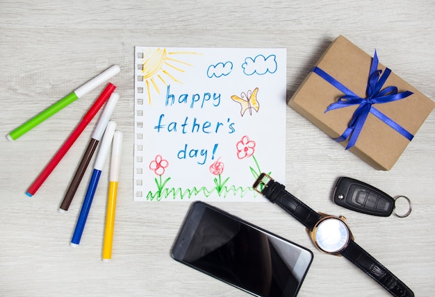 아버지의 날. 남성용 액세서리 옆에 있는 어린이 그림과 선물. 구성 해피 아버지의 날입니다.