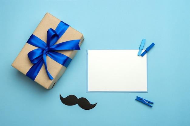 父の日の構成。ブルーのリボン、口ひげ、青の背景に空白のカードのギフトボックス。