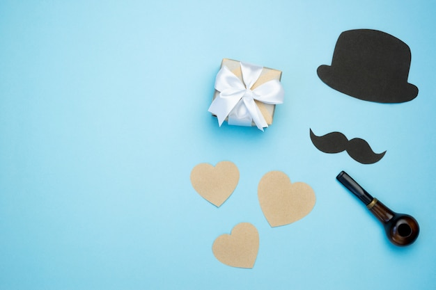 Father's day composition. gift box with hearts and mustache, black hat and pipe on blue background.