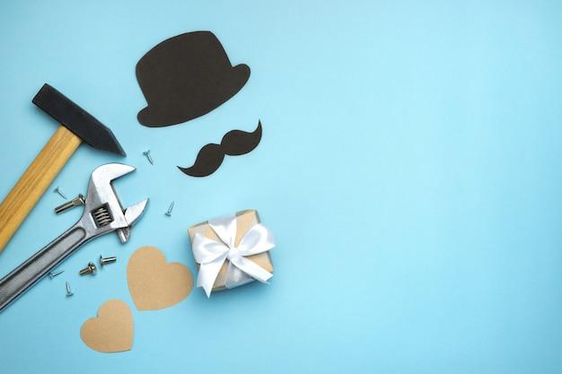 父の日の構成。青い背景に白いリボンの弓、口ひげ、帽子、手のツールのギフトボックス。