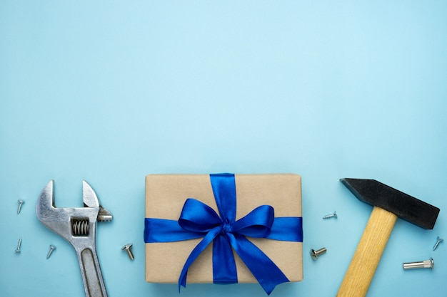 Father's day composition. gift box wrapped in kraft paper with blue ribbon bow and hand tools on blue background.