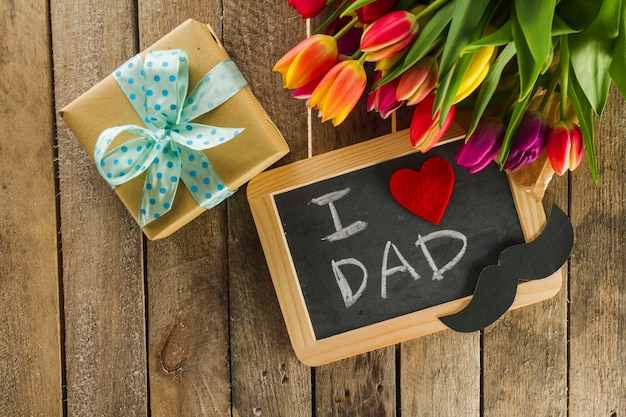 Father's day composition with flowers, slate and gift