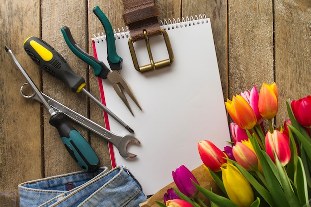 Father's day composition with tools, colored flowers and notebook