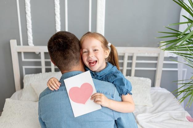 아버지의 날 개념, 소녀 딸이 사랑하는 아버지에게 아버지의 날 하트 카드를 제공합니다.