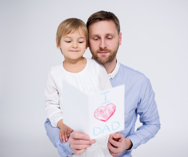 Father's day concept -  little girl giving handmade greeting card to her father over white background