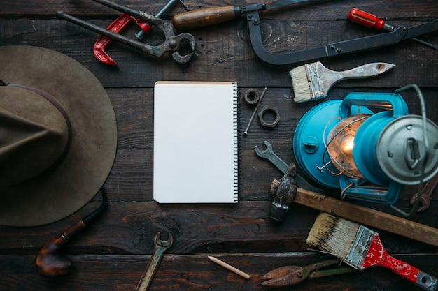 Father's day concept with empty notebook page on vintage workbench top view