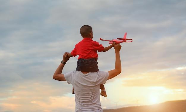 父の日。お父さんと赤ちゃんの息子が一緒に屋外紙飛行機を遊んで