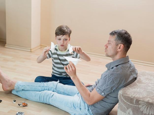 День отца папа и сын играют с бумажными самолетиками