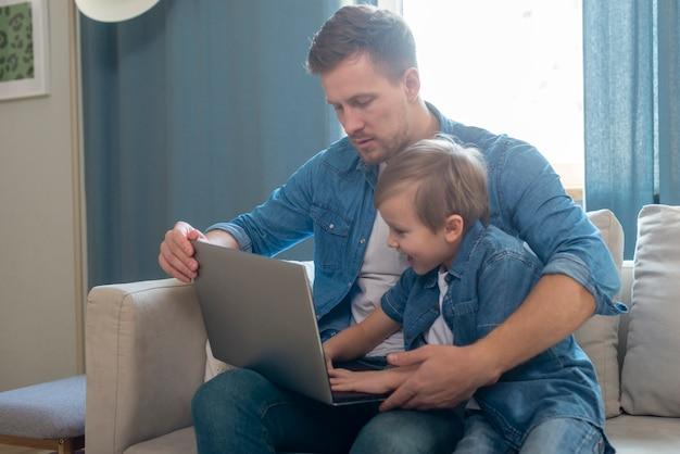 День отца папа и сын, используя ноутбук
