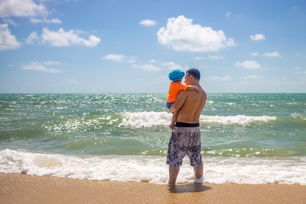 Father's day. dad and baby in his arms look at the sea waves standing on sandy beach.