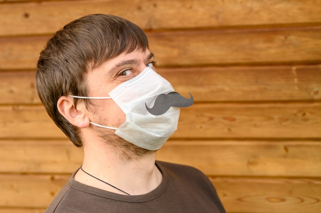 Father's day during the covid-19 quarantine concept. portrait a crazy man in a protective mask and paper moustache against the wall of a wooden wall of the house