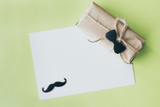 Father's day. gift package wrapped with paper and rope with a decorative bow-tie on green background. copyspace