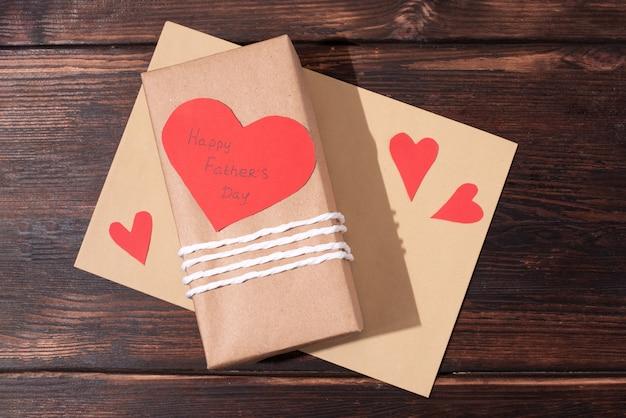 Подарок ко дню отца, завернутый в крафт-бумагу и открытку в форме сердца, конверт.