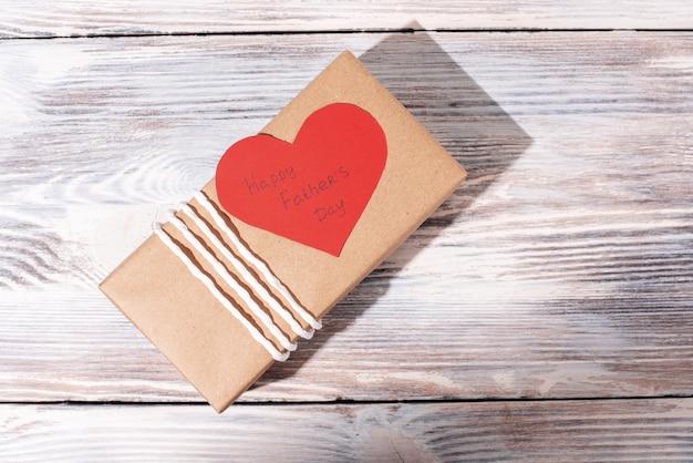 Подарок ко дню отца, завернутый в крафт-бумагу, с поздравительной открыткой в форме сердца