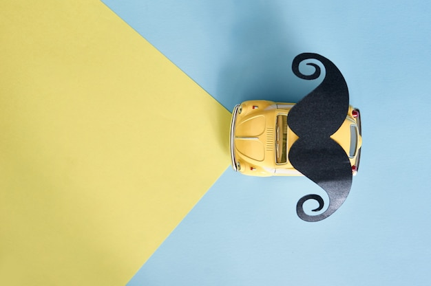 Father's day greeting card with yellow toy car and black paper mustache