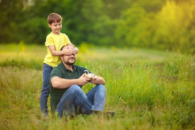 父の日。幸せな父と息子は自然の中で一緒に時間を過ごす、子供は父親に贈り物を与える