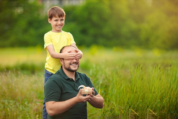 Father's day. happy dad and son spend time together in nature, the child gives his father a gift