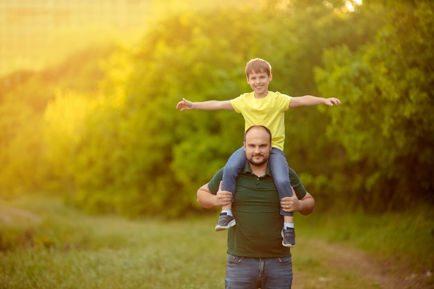 День отца. счастливая семья папа и сын играют на улице, мужчина держит ребенка на плечах