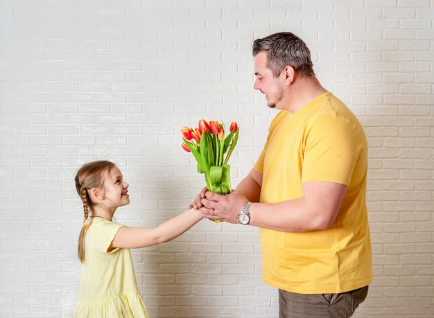 Father's day. happy family daughter giving dad flowers