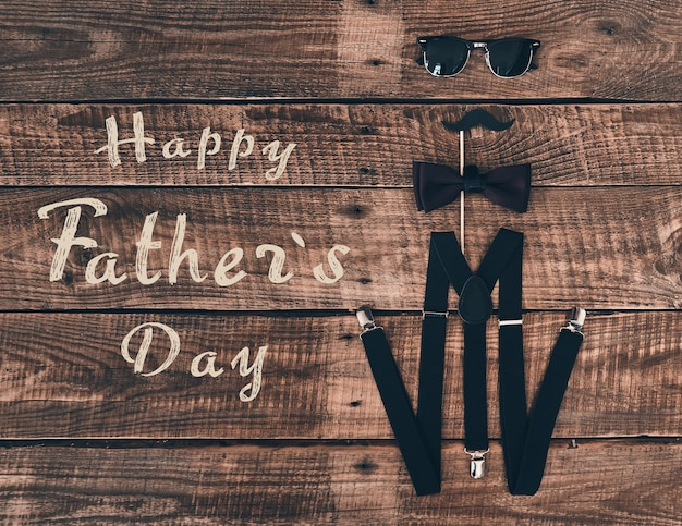 День отца. снимок с высоким углом подтяжек, реквизита, галстука-бабочки и очков, лежащих на деревянном столе