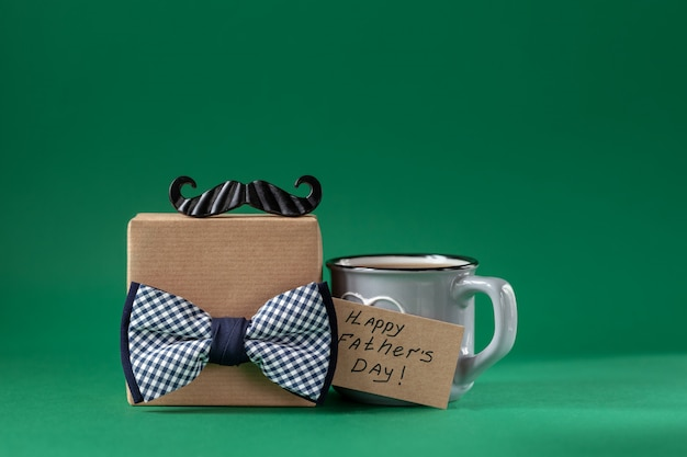 Father's day present gift box with mug coffee on green. holiday present concept.