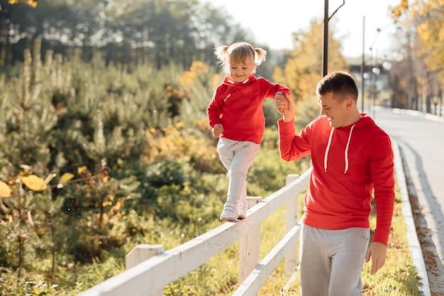 父の日。秋の公園で散歩中に若い幸せな家族の父と娘。