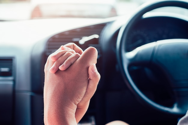 Father's hand holds the daughter's hand while driving