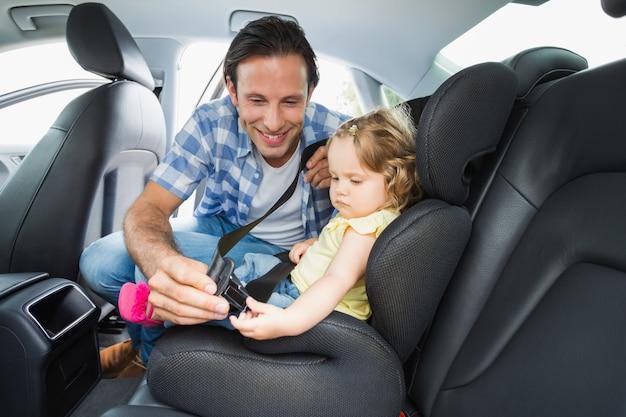 Отец, обеспечивающий ребенка на автокресле