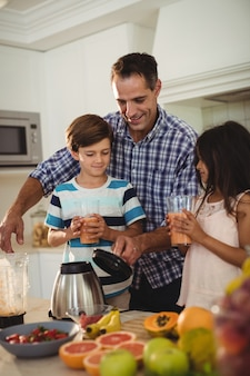Father serving smoothie to his kids in kitchen
