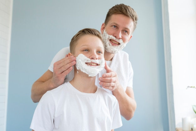Father shaving his son in the bathroom