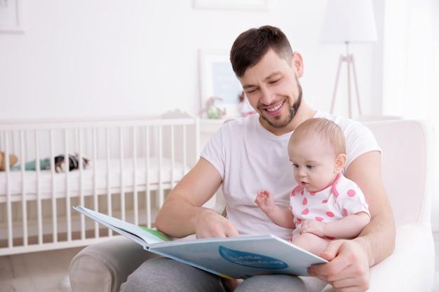 家でかわいい赤ん坊の娘に本を見せている父