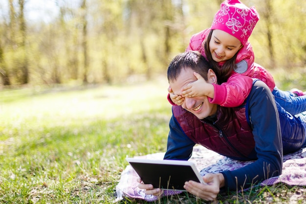 Father showing game in tablet pc to his daughter in the park