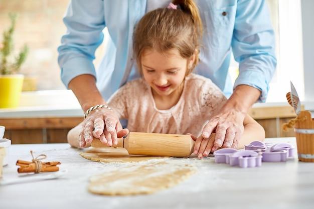 父は幼い娘にクッキーの生地を巻く方法、キッチンで焼く方法、家で家族で料理する方法を教えています。