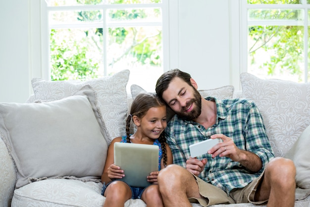 Father showing mobile phone to daughter while sitting on sofa