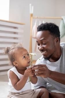 Padre che mostra dei fiori alla sua bambina