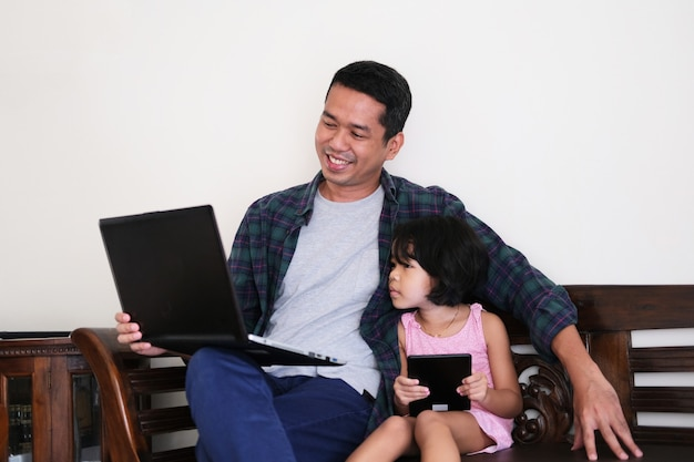 A father showing something in a laptop to his daughter
