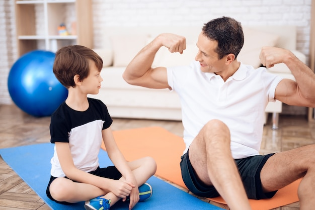 The father shows his son his muscles.