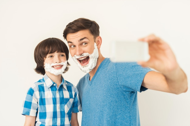 The father shows his son how to shave in the bathroom