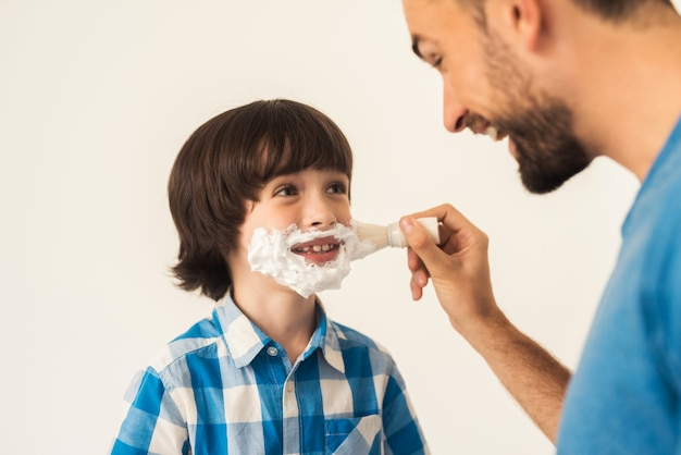 The father shows his son how to shave in the bathroom.