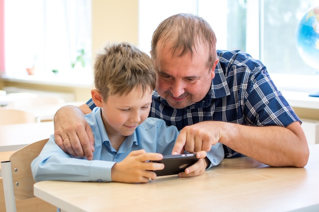 A father shows his son how to use the phone for distance learning