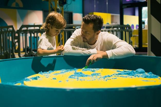 아버지는 아들에게 개발 센터에서 키네틱 샌드로 무엇을 할 수 있는지 보여줍니다. 가족의 관계. 부모의 사랑과 지원. 어린이 발달 센터. 현대 레저.