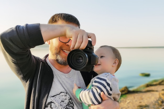 Отец показывает детские фото на камеру на улице