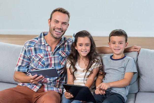 Father and siblings using digital tablet