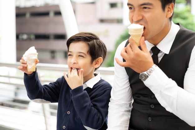 Father single dad and son fill happy eating ice cream cones together on business district urban, dad and son happiness family concept