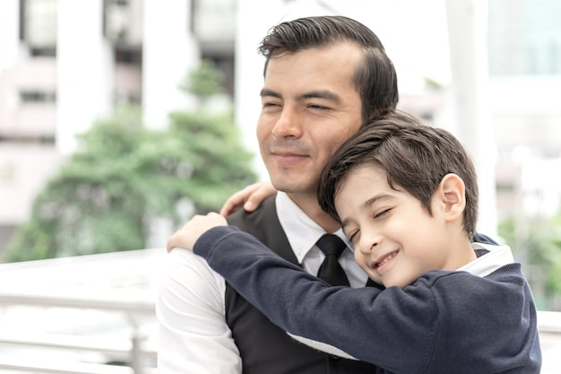 Father single dad and son hugging son on business district urban