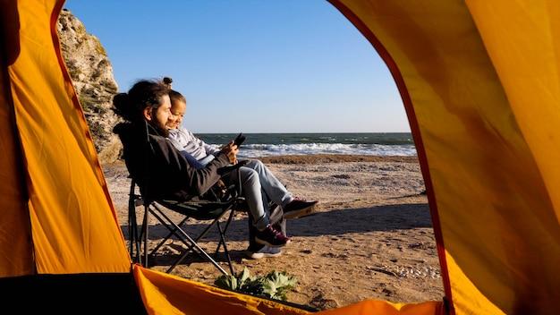 父はキャンプチェアに座って、膝の上に座っている小さな娘のために電子リーダーを読みますo